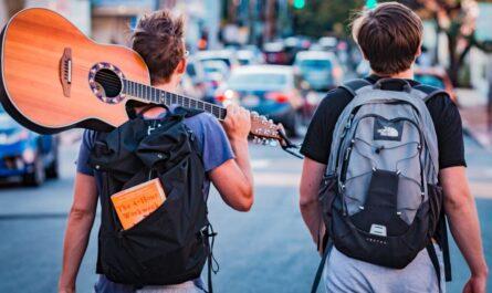 Dva mladíci na cestě, kteří chtějí vyzkoušet autostop.