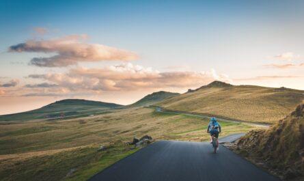 Cyklistu jedoucího po silnici čeká dovolená na kole.